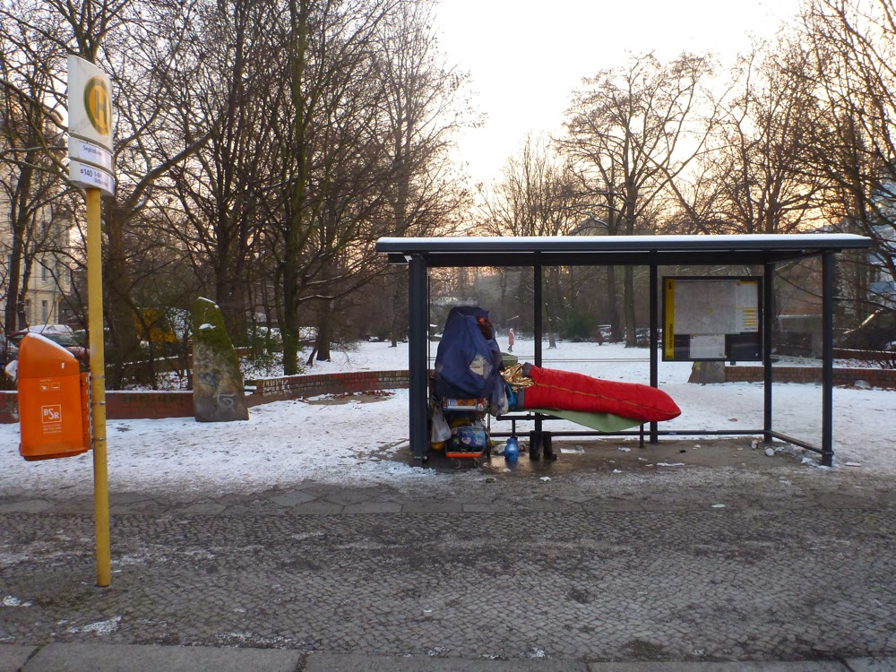 Totale: Bushaltestelle Ritterstraße Ecke Erkelenzdamm, Berlin-Kreuzberg, auf der Sitzbank schläft in rotem Schlafsack ein Obdachloser, seine Habseligkeiten um ihn herum aufgebaut