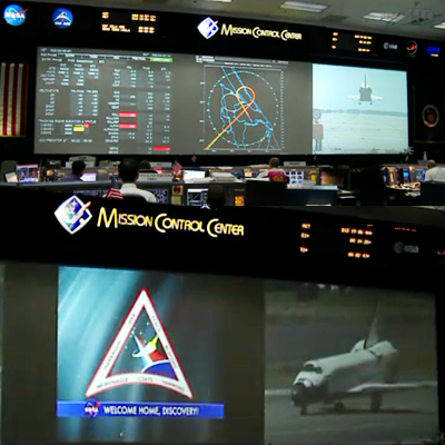 Mission Control Centre at Kennedy Space Centre just before touchdown and after a safe landing with a message of welcome to Shuttle Discovery and Mission STS-133 – 9 March 2011 at 14:57hr UTC. NASA, 2011.