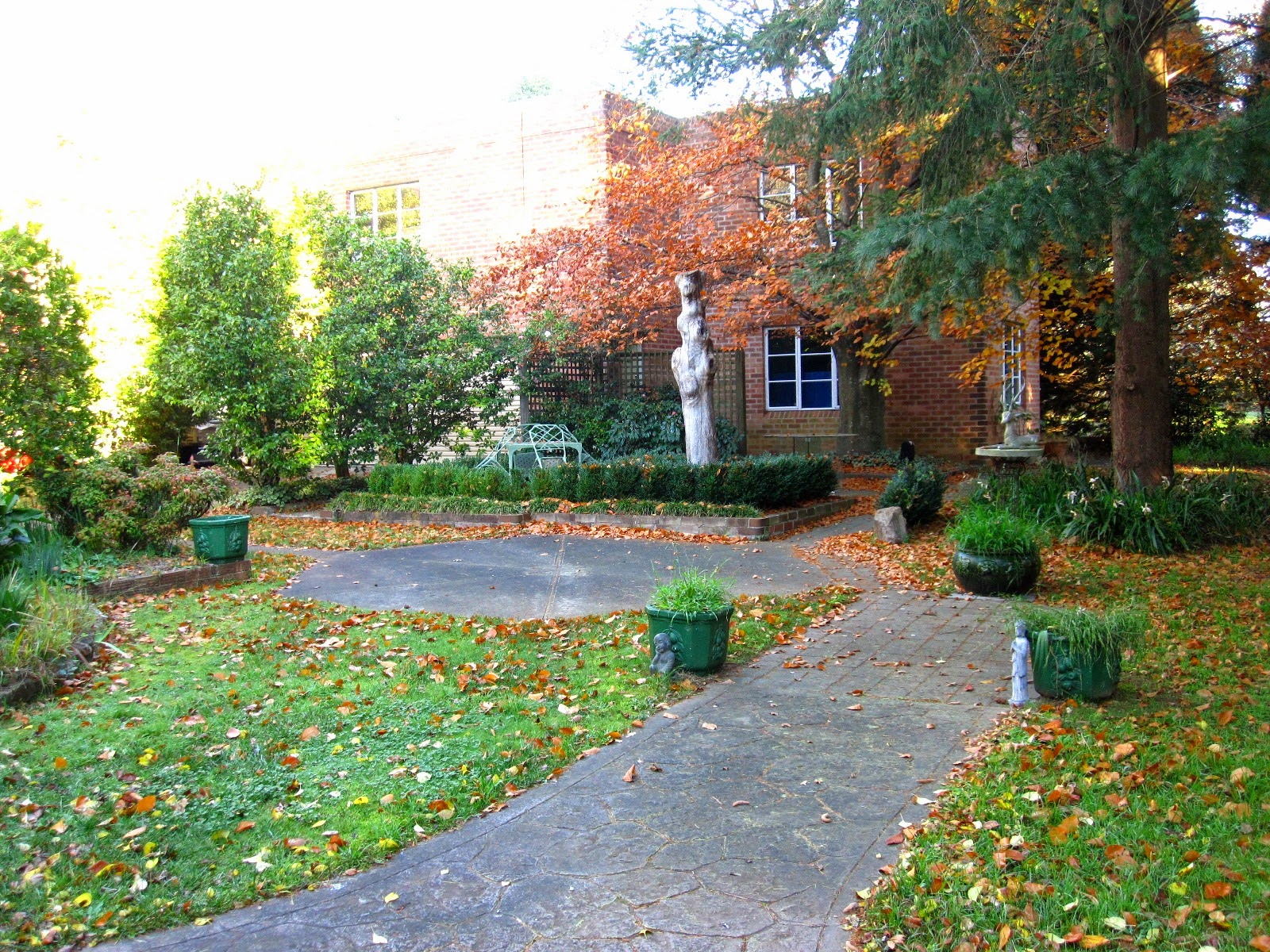 A brick two-storied Art Deco studio in a large garden.