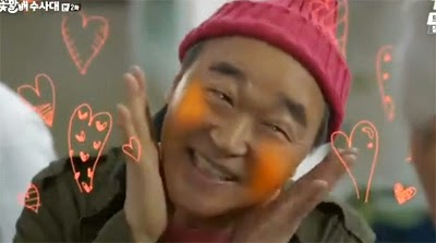 Kang Suk strikes an aegyo pose while pink hearts spring up around him.