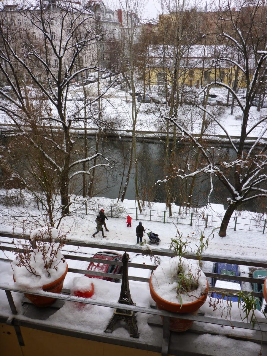 Kanal, Fußgänger, rotgekleidetes Kind, Schnee und Eiffelturmminiatur zwischen den Pflanztöpfen