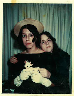 Photograph of two, dark-haired young girls in a photobooth. One is older and wears a hat, and the other hugs her from behind, head on her shoulder. They hold a small ceramic cow.