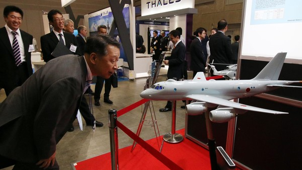 A visitor examines a scale model of Japan's P-1 maritime patrol aircraft