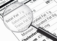 """""""Total fat"""" section of a nutrition label under a magnifying glass"""