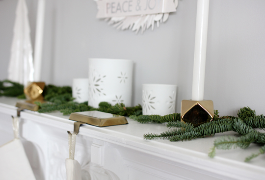 brass candle holders and porcelain candle holders on the mantel