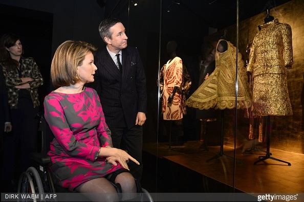 Queen Mathilde of Belgium and fashion designer Dries Van Noten look at creations displayed in the exhibition 'Dries Van Noten. Inspirations