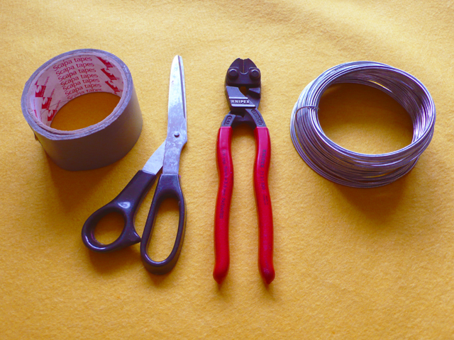 Scalpa tape, scissors, wire cutters and a reel of wire on a yellow felt background.