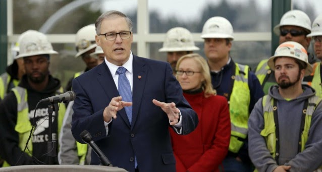 Gov. Jay Inslee speaks at a news conferen ce as he stands with state Transportation Secretary Lynn Peterson and construction workers Tuesday, Dec. 16, 2014, in Medina, Wash. (Credit: AP Photo/Elaine Thompson) Click to Enlarge.