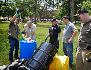 Participants practice techniques to retrieve liquids from chemical drums.