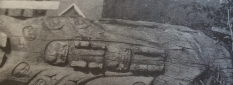 Black and white image. Portion of wooden totem pole.