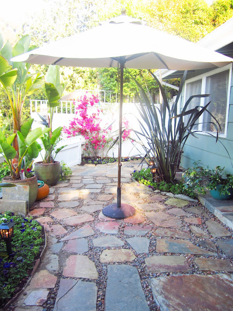 Backyard with umbrella, shrubbery, lanterns and potted plants