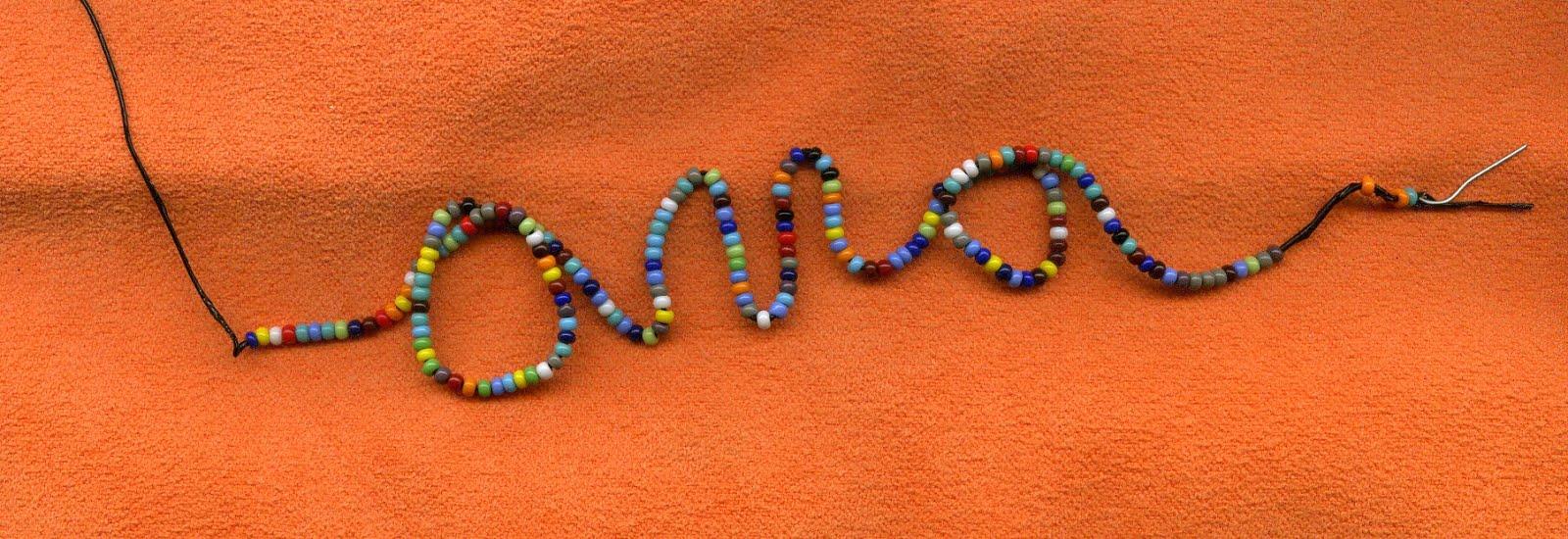 La palabra ama hecha con alambre y chaquiras