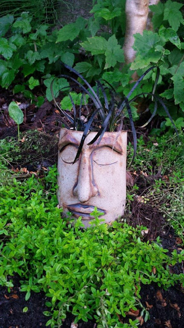 Peaceful ceramic / pottery garden planter head out in the garden.