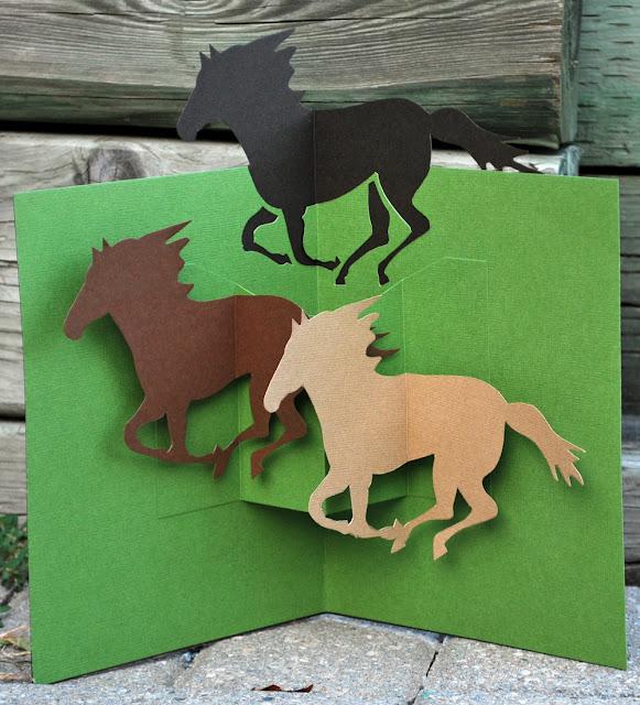 самодельная открытка-раскладушка с силуэтами скачущих лошадей на зеленом поле