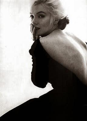 Photographie de Marilyn monroe noi et blanc, blonde platine, avec une robe noire dos décolleté, image triste