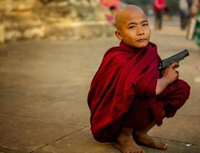 Buddhist child with a gun, crouching