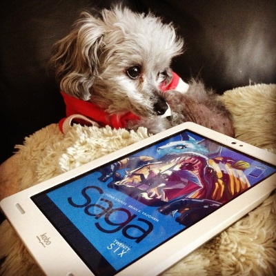 Murchie lays on a fuzzy white pillow. His head is twisted slightly to the left so he appears in profile. In front of him is a white Kobo with the cover of Saga #26/Volume Five on its screen. The blue-toned cover features a cloaked black woman using a spear to prop open a monster's mouth while a smaller person tumbles out of it. A hairless blue cat looms behind the monster.