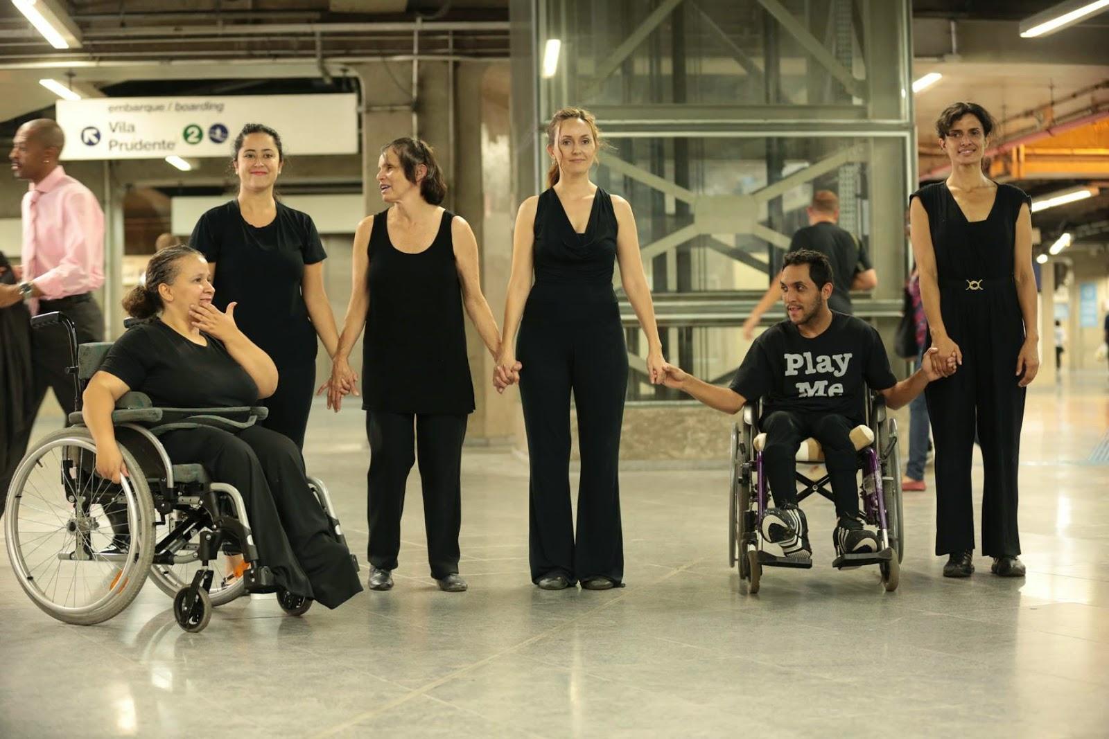 Descrição da Foto: Seis intérpretes vestidos de preto estão na plataforma do metrô. Dois deles estão numa cadeira-de-rodas. A maioria deles está de frente, mãos dadas, sorrindo. Pessoas passam, placas de sinalização no alto e elevador no fundo.