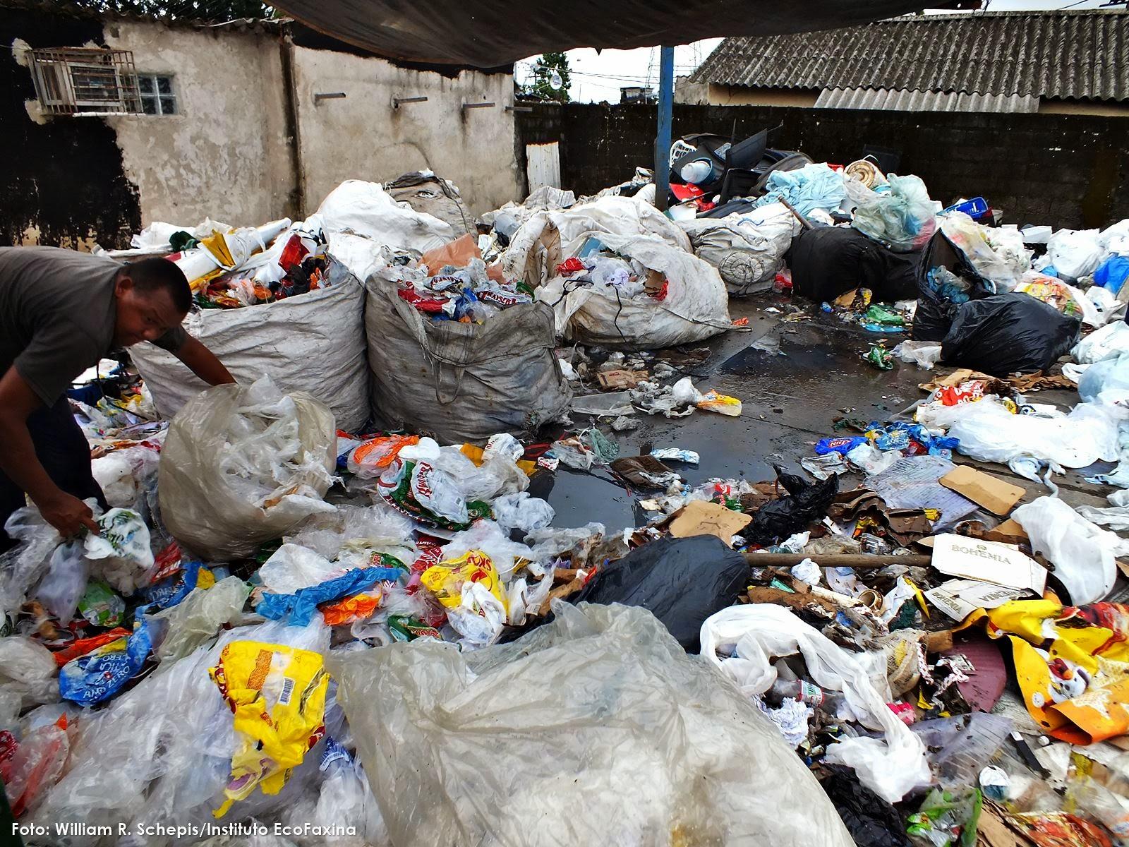 Pessoas separam resíduos sem o uso de equipamentos de proteção individual.