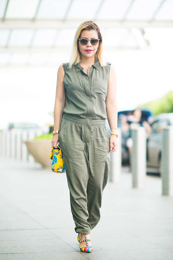 Crystal Phuong in airport attire army green jumpsuit and multi colors rockstud heels