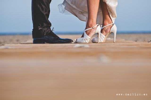 zapatos de novio y novia sobre pasarela de madera en la postboda de playa