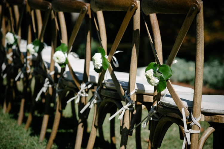 wedding day decor with white flower tied onto tuscan cafe chair