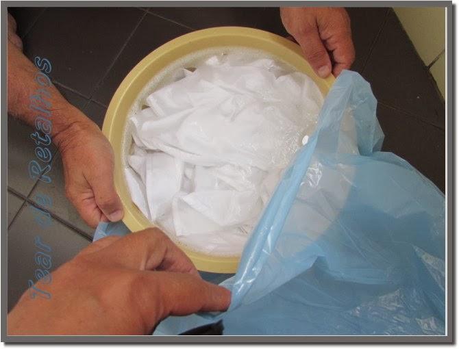 Colocando a bacia com a roupa branca encardida no molho dentro de um saco plástico azul.