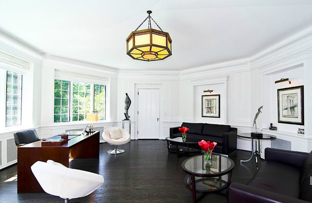 Oval home office with leather furniture, dark wood floors and an octagon pendant light