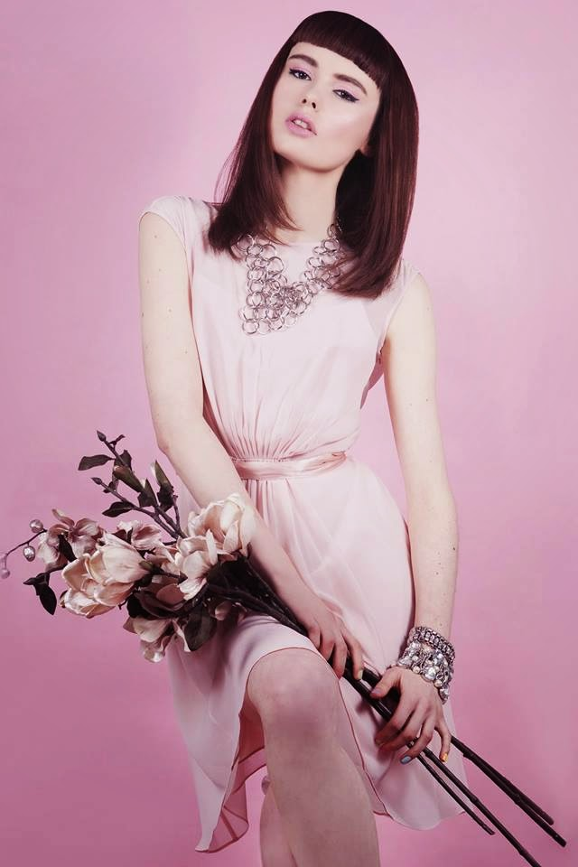 Girl modelling pretty pastel clothes holding flowers on a fashion shoot