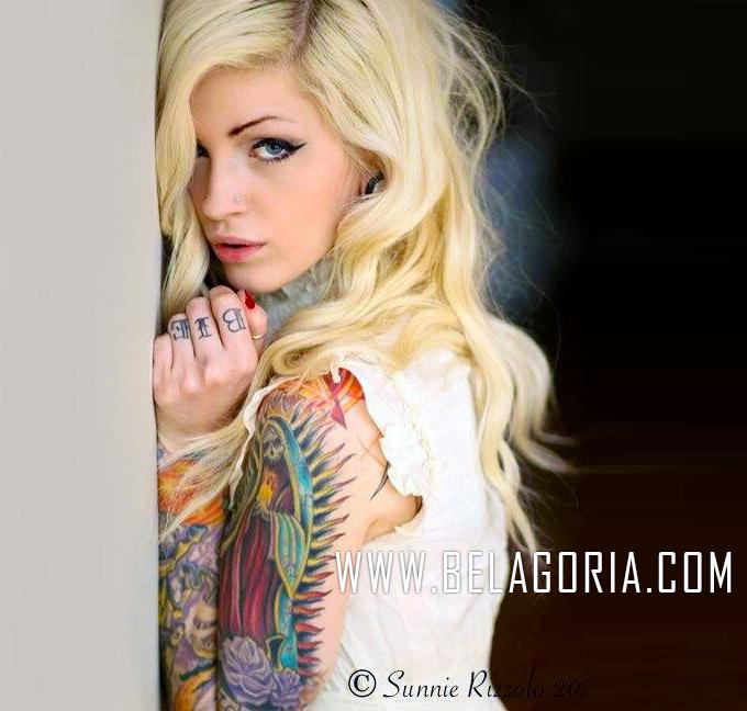 Mujer rubia apoyada en muro, lleva un tatuaje de la santa muerte en el brazo izquierdo