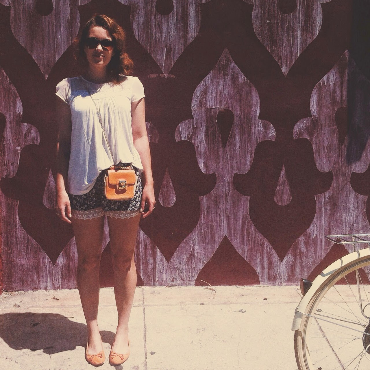 Los Angeles based style blogger wears summer look of floral shirt and breezy top with lace details for a bike ride