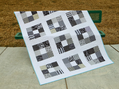 a patchwork quilt draped over a park bench made using only black and white fabrics
