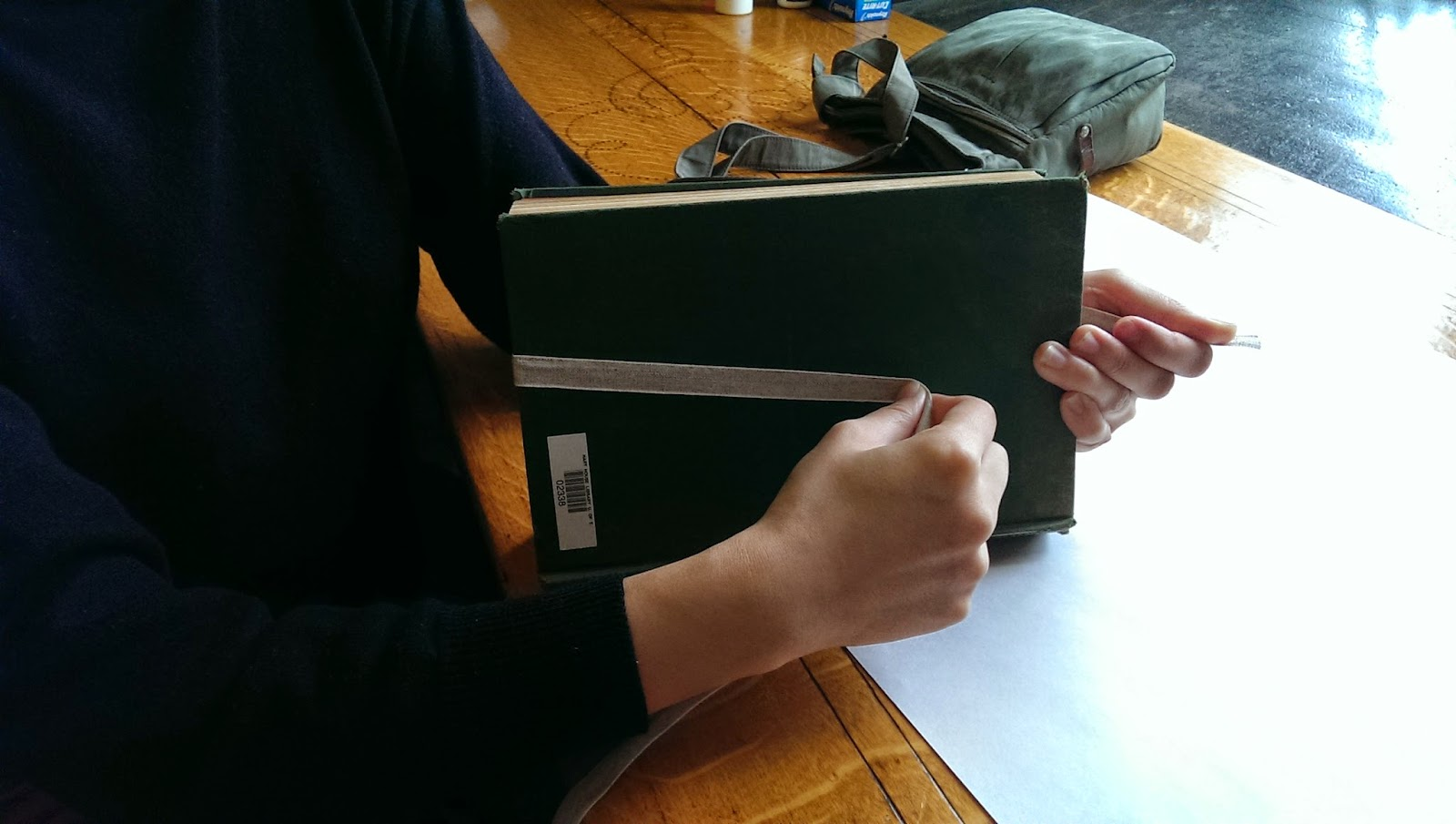 A girl in a long-sleeved blue shirt ties a length of archival tape around an old book to stabilize it