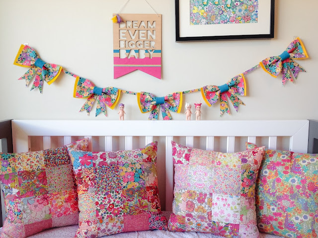 Liberty Patchwork Cushions Displayed on Baby Cot Bow Garland Bunting