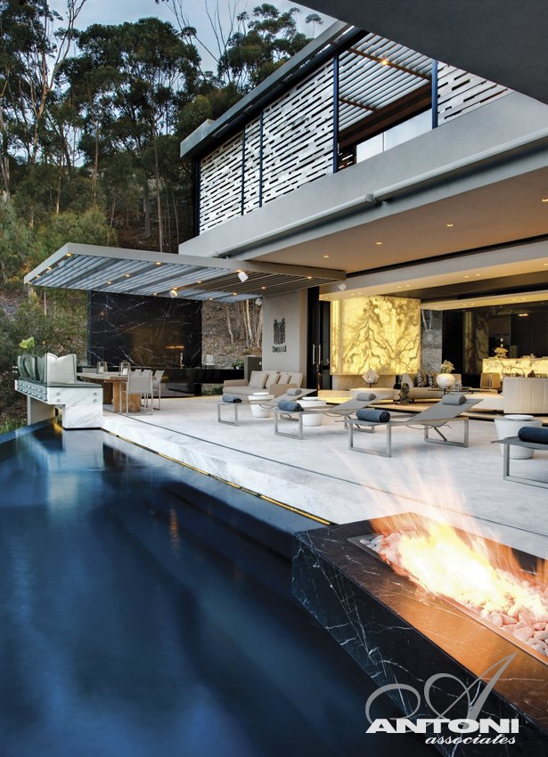 Fireplace by the swimming pool at Head Road 1843 by Antoni Associates