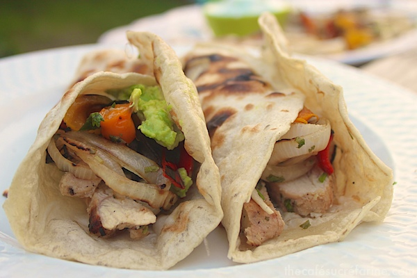 Side photo of two Grilled Chicken Fajitas on a white plate.