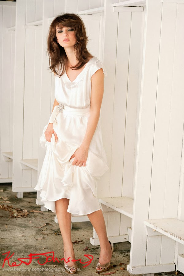 Full length white satin Wedding dress, white timber walls, location fashion photographed by Kent Johnson.