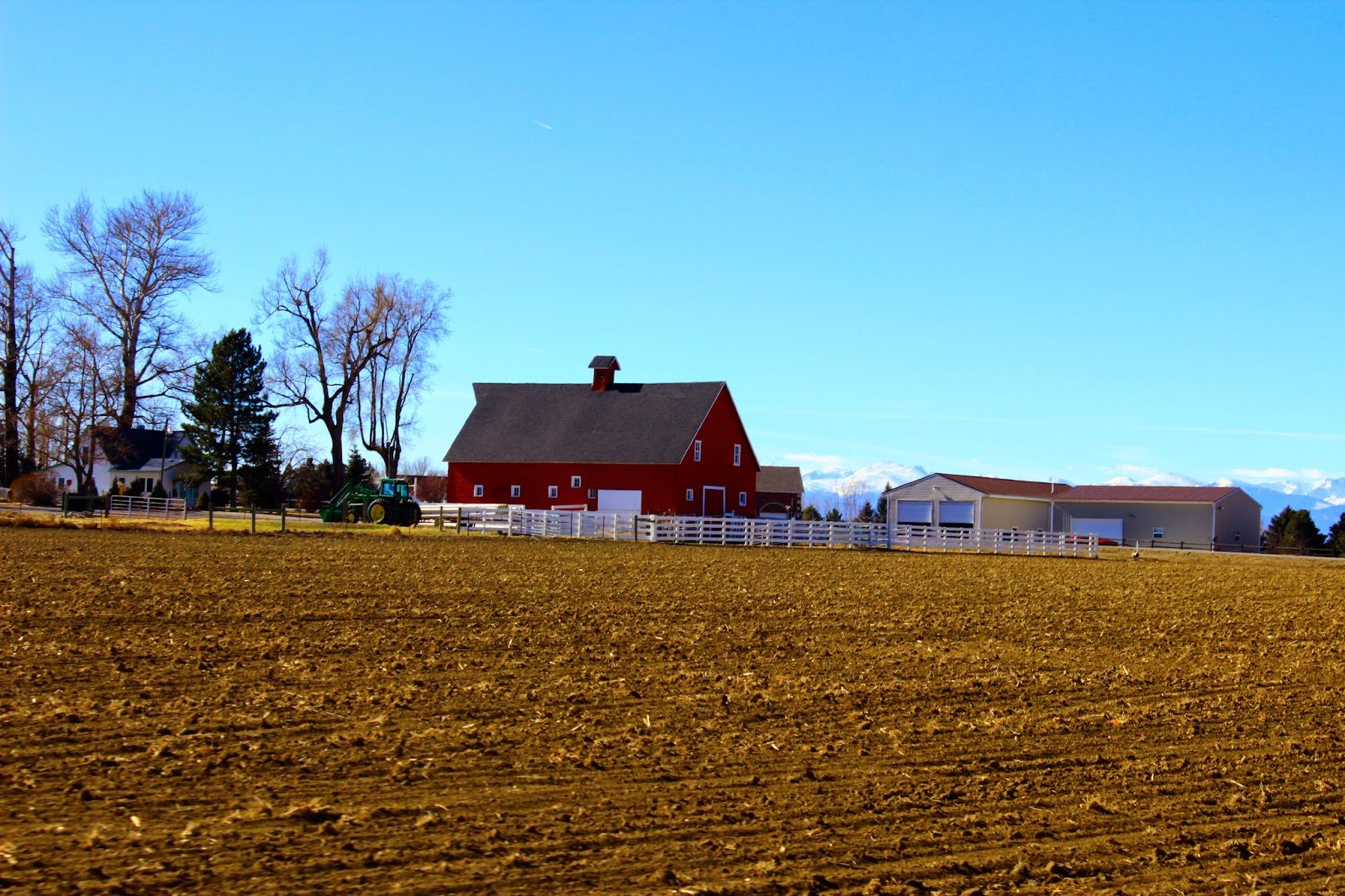a big red barn sits next to some plowed farmland