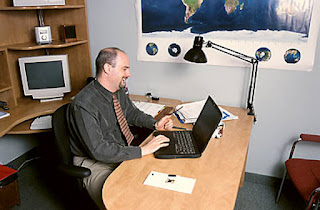 business man using the telephone and a laptop computer on a desk