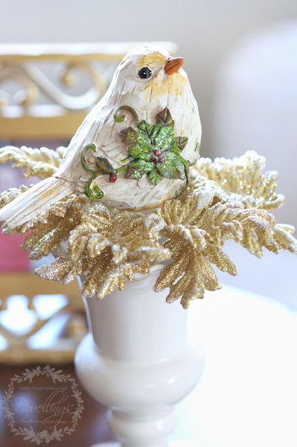 Christmas birds on glittery gold ornament just on top of a vase.