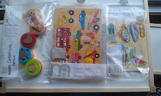 Three different colourful wooden puzzles, bagged in the zip-lock sleepsuit packages.