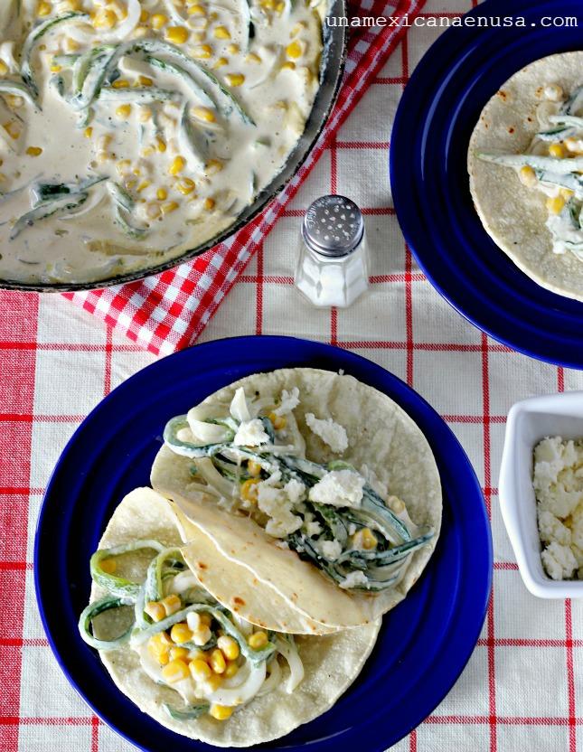 Mesa con una sartén con rajas de chile poblano y tacos de rajas en un plato.