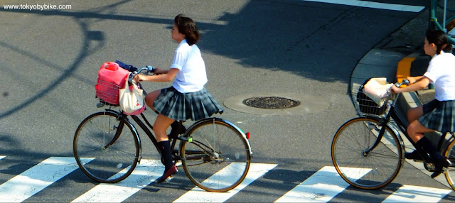 Schoool girls cycling to school in Tokyo Japan