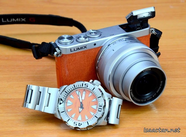 The Lumix GM1 with lens extended, flash popped up, photographed with my matching Seiko Orange Monster watch