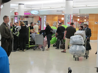 Cuban-Americans checking in huge poly-wrapped baggage at MIA