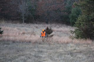 photo of a coyote hunter in a field
