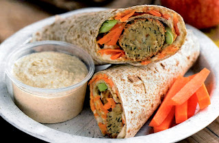 Home-made tortillas wrapped around falafel and mixed vegetables sliced in half and served with chickpea hummus and carrot sticks