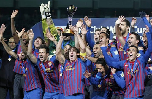 Barcelona captain Carles Puyol holds the Club World Cup trophy on the podium