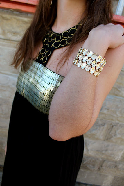 Black maxi dress with gold details and gold bracelet