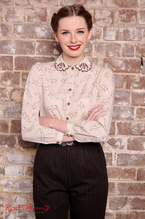 Brown pin stripe pants, lace collar dove print blouse, mid shot - photographed against a distressed brick wall in the studio - studio fashion photography